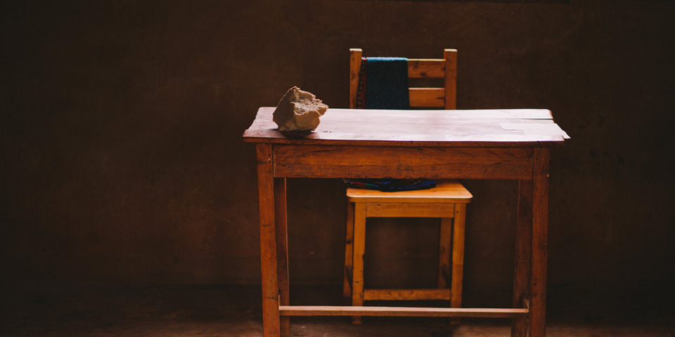 A simple chair and desk in a Rwandan classroom